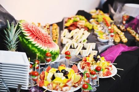 mesa para banquetes: primer plano pulido de alimentos de frutas, verduras, carnes y pescados dispuestos sobre la mesa de banquete