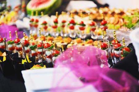 buffed food closeup of  fruits, vegetables, meat and fish arranged on banquet table