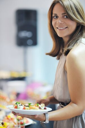 womanl chooses tasty meal in buffet at hotel  banquet party restaurant Stock Photo - 10601818
