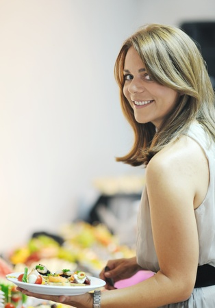 buffet dinner: womanl chooses tasty meal in buffet at hotel  banquet party restaurant Stock Photo