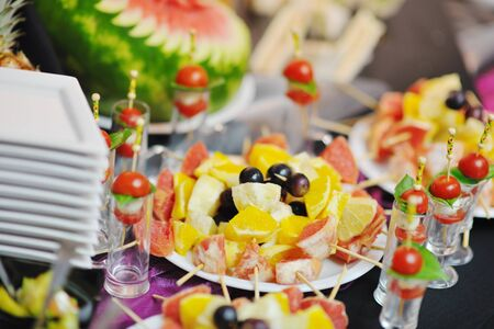 buffed: buffed food closeup of  fruits, vegetables, meat and fish arranged on banquet table