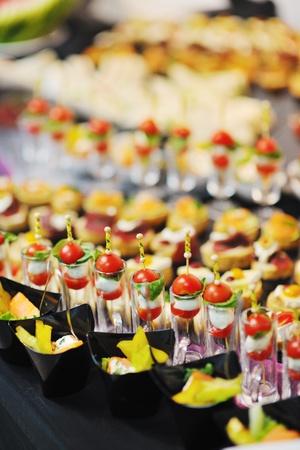 buffet food: primer plano pulido de alimentos de frutas, verduras, carnes y pescados dispuestos sobre la mesa de banquete