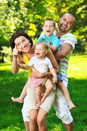 子供たちと幸せな若いカップルは、美しい公園の自然の中で屋外で楽しい時を過す