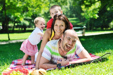 weekends: happy young couple with their children have fun at beautiful park outdoor in nature