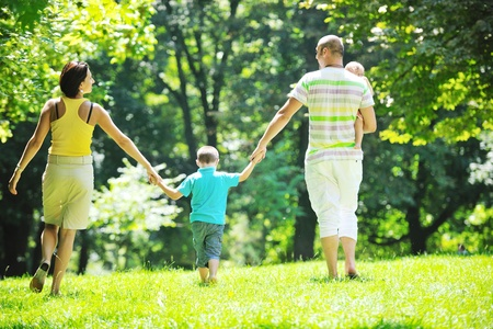 happy young couple with their children have fun at beautiful park outdoor in nature photo