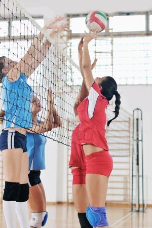 pelota de voley: voleibol de juego deportivo con un grupo de j�venes hermosas chicas en el deporte bajo techo campo