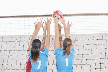 pelota de voleibol: voleibol el deporte juego con un grupo de jóvenes hermosas chicas en el deporte bajo techo arena