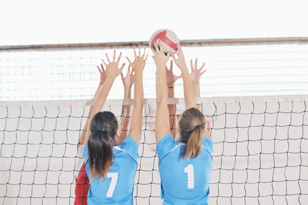 team winner: volleyball game sport with group of young beautiful  girls indoor in sport arena Stock Photo