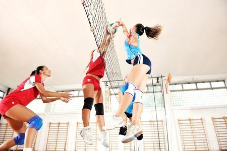 pelota de voley: deporte juego de voleibol con el grupo de jóvenes chicas guapas indoor en arena de deporte