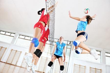 pelota de voleibol: deporte juego de voleibol con el grupo de jóvenes chicas guapas indoor en arena de deporte