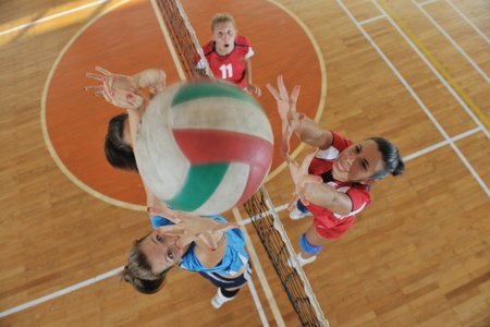 volleyball serve: volleyball game sport with group of young beautiful  girls indoor in sport arena Editorial