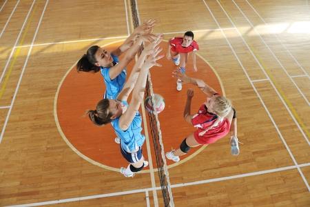 pelota de voley: voleibol el deporte juego con un grupo de jóvenes hermosas chicas en el deporte indoor arena