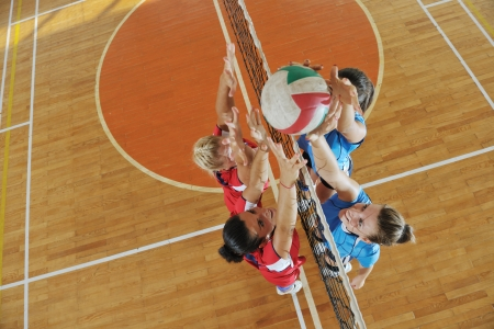 pelota de voley: deporte juego de voleibol con el grupo de j�venes chicas guapas indoor en arena de deporte