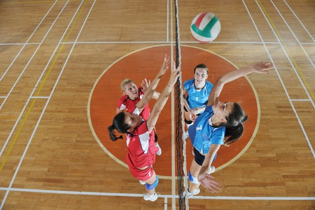 pelota de voleibol: voleibol el deporte juego con un grupo de j�venes hermosas chicas en el deporte bajo techo arena