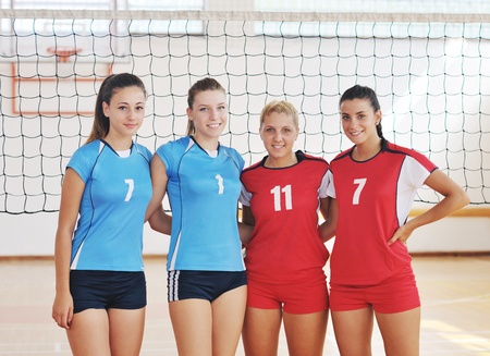 athletic girl: volleyball game sport with group of young beautiful  girls indoor in sport arena Stock Photo