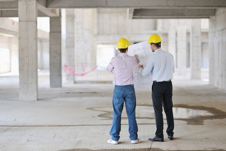 project manager: Team of business people in group, architect and engeneer  on construciton site check documents and business workflow on new building
