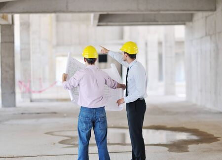 Team of business people in group, architect and engeneer  on construciton site check documents and business workflow on new building photo