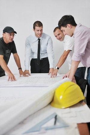 construction paper: Team of business people in group, architect and engeneer  on construciton site check documents and business workflow on new building