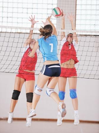 pelota de voley: voleibol de juego deportivo con un grupo de jóvenes hermosas chicas en el deporte bajo techo campo