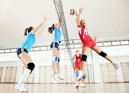 pelota de voley: voleibol el deporte juego con un grupo de jóvenes hermosas chicas en el deporte bajo techo arena