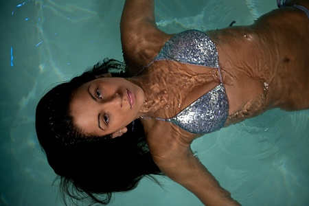 Closeup of pretty young lady have fun and posing  while relaxing in the swimming pool in luxury hotel photo