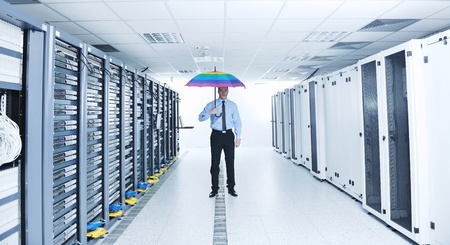 young handsome business man  engineer in   businessman hold  rainbow colored umbrella in server datacenter room  and representing security and antivirus sofware protection concept photo