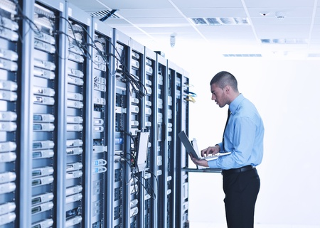 computer hardware: young engeneer business man with thin modern aluminium laptop in network server room