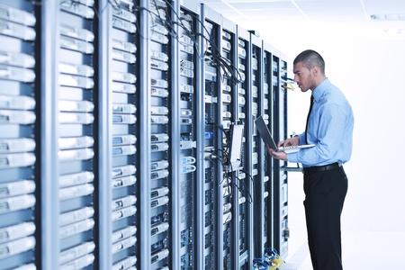 сеть: Молодой деловой человек, инженер с тонким современных алюминиевых ноутбука в сети серверной комнате