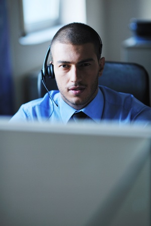 helpline: businessman with a headset portrait at bright call center helpdesk support office Stock Photo