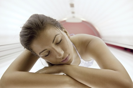 sunspot: Beautiful young woman have tanning skin treatment in modern solarium