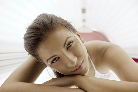 ultraviolet: Beautiful young woman have tanning skin treatment in modern solarium