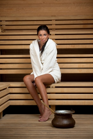 bathhouse: Pretty Young woman take a steam bath treatment at finish wooden sauna while wearing white towel