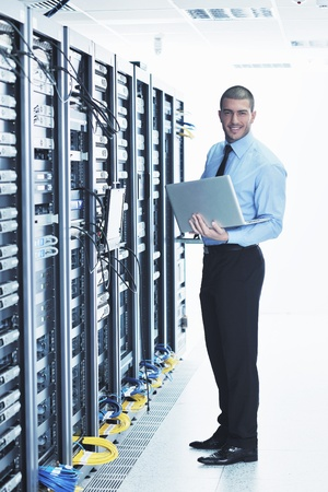 isp: young engeneer business man with thin modern aluminium laptop in network server room