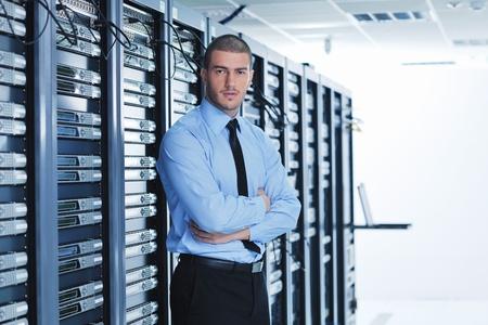 service center: young handsome business man  engeneer in datacenter server room