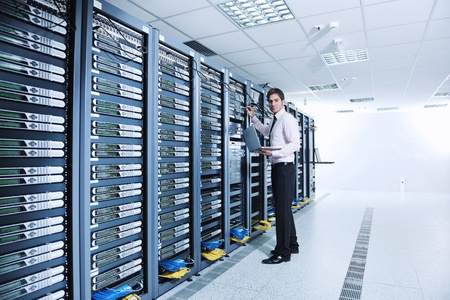young engeneer business man with thin modern aluminium laptop in network server room Stock Photo - 11022962