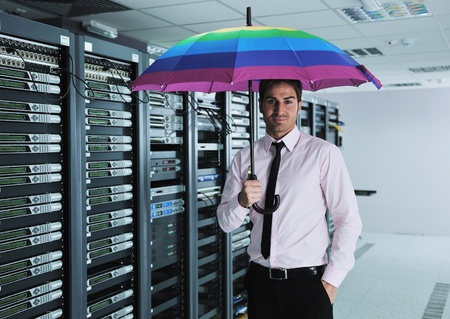 young handsome business man  engineer in  businessman hold  rainbow colored umbrella in server datacenter room  and representing security and antivirus sofware protection concept Stock Photo - 11022707