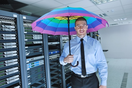 datacenter: young handsome business man  engineer in   businessman hold  rainbow colored umbrella in server datacenter room  and representing security and antivirus sofware protection concept
