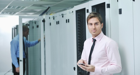 young business man computer science engeneer talking by cellphone at network datacenter server room asking  for help and fast solutions and services Stock Photo - 11022702