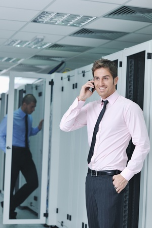 engeneer: young business man computer science engeneer talking by cellphone at network datacenter server room asking  for help and fast solutions and services Stock Photo