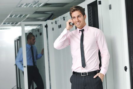 young business man computer science engeneer talking by cellphone at network datacenter server room asking  for help and fast solutions and services Stock Photo - 11022771