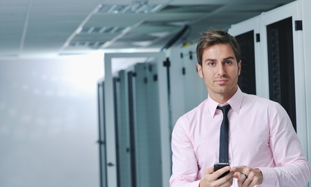 fast service: young business man computer science engeneer talking by cellphone at network datacenter server room asking  for help and fast solutions and services Stock Photo