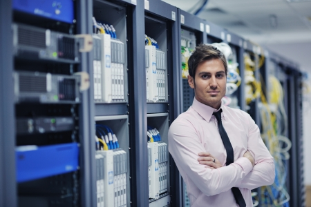 データ センターのサーバー ルームに若いハンサムなビジネス人エンジニア