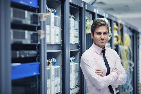 communication industry: young handsome business man  engeneer in datacenter server room