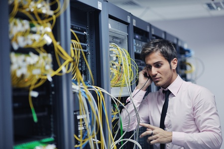 phone support: young business man computer science engeneer talking by cellphone at network datacenter server room asking  for help and fast solutions and services Stock Photo
