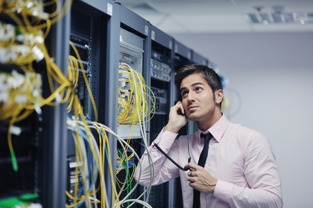 young business man computer science engeneer talking by cellphone at network datacenter server room asking  for help and fast solutions and services Stock Photo - 11022906