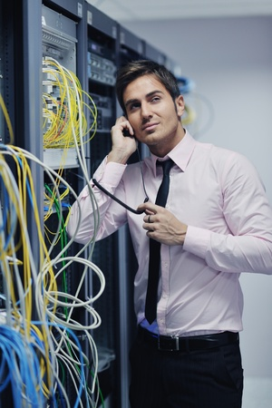 network cables: young business man computer science engeneer talking by cellphone at network datacenter server room asking  for help and fast solutions and services Stock Photo