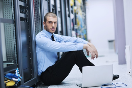 young engineer business man with thin modern aluminium laptop in network server room photo