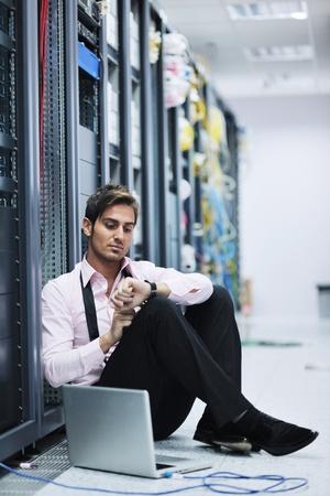 hombre flaco: ingeniero joven hombre de negocios con la computadora portátil delgada de aluminio moderna en la sala de servidor de red