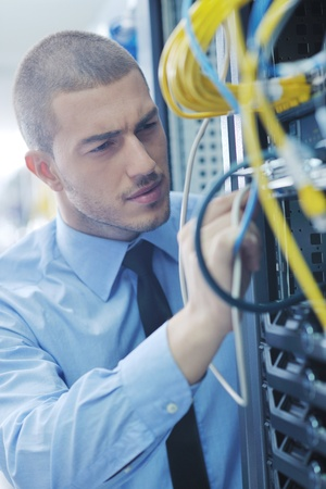 cable tv: young handsome business man  engeneer in datacenter server room