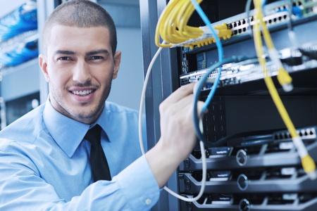 data server: young handsome business man  engeneer in datacenter server room